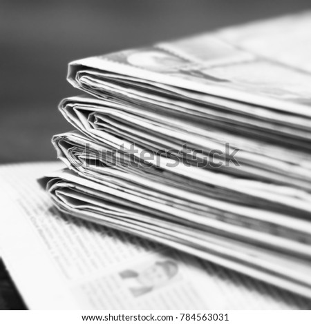 Newspapers for background. Old English daily papers with news on the table. Pages with headlines and articles folded and stacked, grange style. Blurred retro texture.                                   #784563031