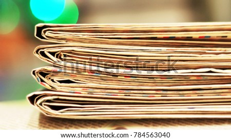 Newspapers for background. Old English daily papers with news on the table. Pages with headlines and articles folded and stacked, grange style. Blurred retro texture.                              #784563040