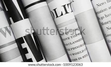 Newspapers. Headlines and articles shown partially in a stack of daily papers with news #1009123063