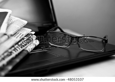 Newspapers laptop glasses in composition black and white