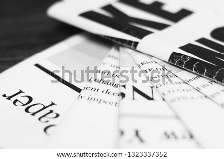 Newspapers with headlines and articles scattered on horizontal surface, background texture                          #1323337352