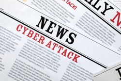 Newspapers with headlines Cyber Attack as background, closeup