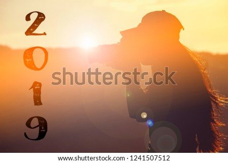 Newyear 2019 Silhouette young woman. Hipster girl photographer taking Photo at sunrise Travel adventure in Destination. Nature Explore, outdoor mountain traveling. Travel woman at Sun.