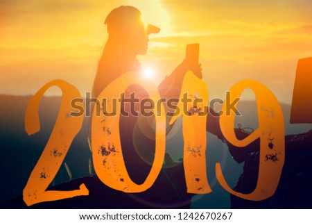 Newyear 2019 Silhouette young woman.Hipster girl photographer taking Photo by Smartphone at sunrise Travel adventure in Destination. Nature Explore, outdoor mountain traveling. Travel woman at Sun.