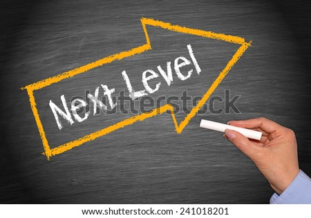 Next Level - female hand with chalk and arrow on blackboard background