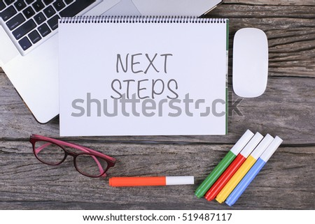 NEXT STEPS text on wooden desk with tablet pc and keyboard #519487117
