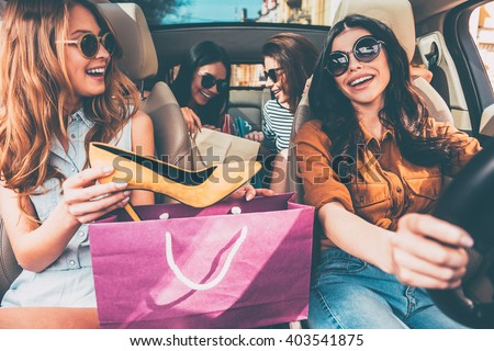 Next stop is lingerie shop! Four beautiful young cheerful women holding shopping bags and looking at each other with smile while sitting in car #403541875