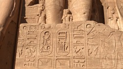 Next to the colossal statues of Ramesses's legs are smaller statues of his chief wife, his queen mother and his children.