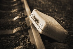 Next to the railway is an old worn-out retro suitcase, forgotten during the trip. 20th century. Immigration. Sepia.