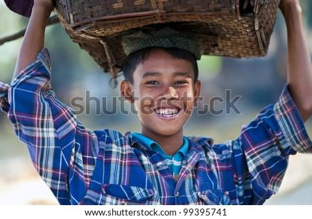 NGAPALI, BURMA - JANUARY 21: Smiling boy Thin Moe, 11 with basket posing for the photo during the Hta-Mane Festival on January 21, 2011 in Ngapali, Burma