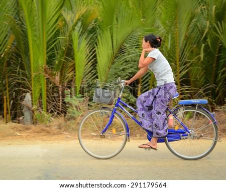 Ngapali, Myanmar - Jan 22, 2015. Burmese woman rides bicycle along countryside street in Ngapali, Myanmar.