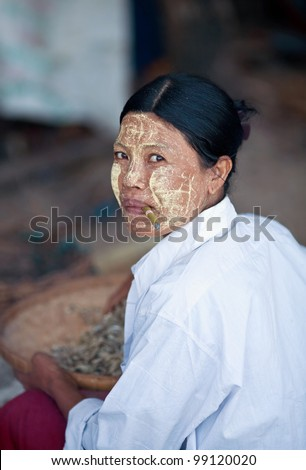 NGAPALI, MYANMAR - JANUARY 21: An unidentified Burmese woman with thanaka paste on the face posing for the photo during the Hta-Mane Festival on January 21, 2011 in Ngapali, Myanmar - stock photo