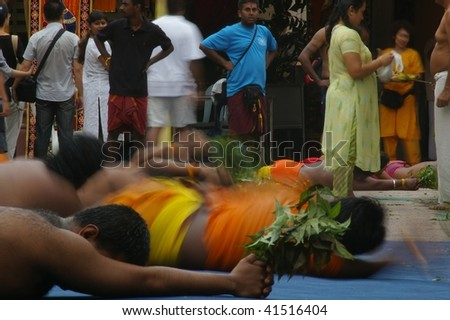 NGAPORE, SINGAPORE - NOVEMBER 04: Hindus doing ritual rolling (Angapirathatchanam) at Sri Mariamman Temple for the Thimithi Festival  November 04, 2009 in Ngapore, Singapore.