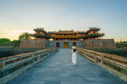 Ngo Mon gate - the main entrance of forbidden Hue Imperial City in Hue city, Vietnam, with Vietnamese girl wearing traditional dress Ao Dai