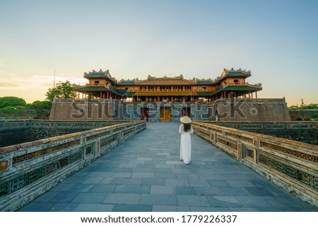 Photo of  Ngo Mon gate - the main entrance of forbidden Hue Imperial City in Hue city, Vietnam, with Vietnamese girl wearing traditional dress Ao Dai