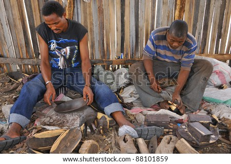 NGOROGORO -TANZANIA, OCTOBER 20: Masai woodcarver work in the workshop with ebony wood on October 20 Ngorogoro, Tanzania. The Maasai are a Nilotic group in East Africa, next to the Indian Ocean.