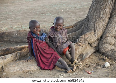 NGORONGORO CONSERVATION AREA, TANZANIA - JANUARY 24: Pair of unidentified African children smile on January 24, 2008. Children from Masai tribe sit on a root tree in a village near Ngorongoro crater.