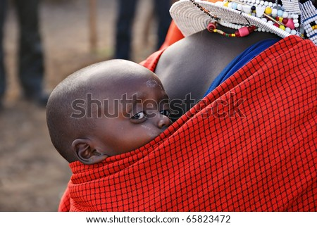 NGORONGORO CONSERVATION AREA, TANZANIA - JANUARY 24: Unidentified African child from Masai tribe on January 24, 2008.  Very young child is on the back of his mother - stock photo