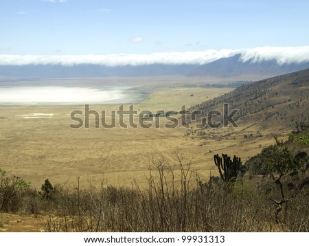 Ngorongoro crater with clouds hanging over the rim and lake Magadi in white.