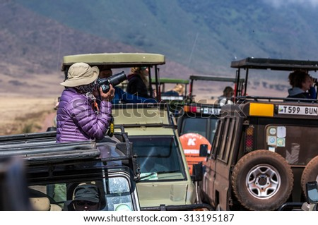 NGORONGORO ,TANZANIA - AUGUST 2nd 2015 ; Big group of tourists in safari cars enjoy the wildlife of the park. Ngorongoro Creater, Tanzania, Africa