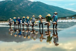 NhaTrang, Vietnam. Women carry salt from salt farm to factory.