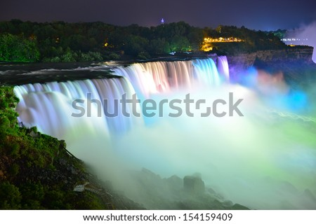 Niagara Falls lit at night by colorful lights, Niagara, NY, USA