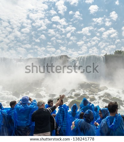 NIAGARA FALLS, USA - JULY 8: Tourists look at The American Falls from boat on July 8, 2012. The American Falls is one of three waterfalls that together are known as Niagara Falls.