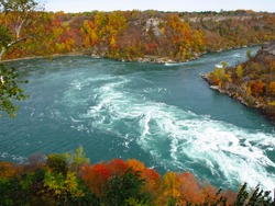 Niagara Whirlpool rapids, located on the Canadian and American border. In the background the incredible colors of Autumn, trees with red, orange, yellow and green leaves.