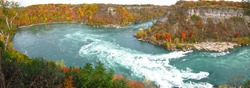 Niagara Whirlpool rapids panoramic view, located on the Canadian and American border. In the background the incredible colors of Autumn, trees with red, orange, yellow and green leaves.