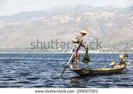 NIAUNGSHWE, MYANMAR - FEBRUARY 2, 2015: A fisherman at lake Inle, Myanmar stands in his boat, rows with one leg, and handles the net. In the background are the mountains.