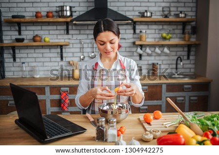 Nice adult woman sit at table in kitchen. She break eggs and pour them into bowl. Model look down. She concentrated. Woman wear apron. #1304942275