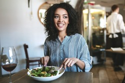 Nice African American girl with dark curly hair eating in restaurant. Smiling girl sitting at cafe and looking aside with glass of red wine and salad on table. Portrait of lady at lunch in restaurant