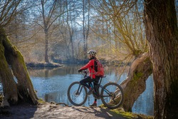 nice and active senior woman ring her electric mountain bike on a sunny day in early spring at river Enz in Baden-wuerttemberg, Germany