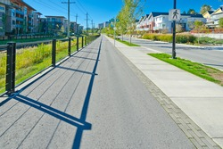Nice and clean long pedestrian sidewalk at the empty street in the comfortable neighborhood in the suburbs of Vancouver, Canada.