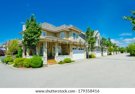 Nice and comfortable neighborhood. A House on the corner of empty street and a row, line of the houses with garages, homes in the suburbs of the North America. Canada.