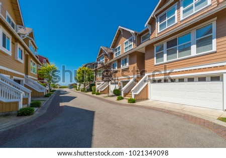 Nice and comfortable neighborhood. Some homes, condos, townhouses on the empty street in the suburbs of Vancouver, Canada.