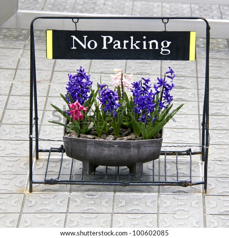 Nice and polite No Parking sign with pot of flowers