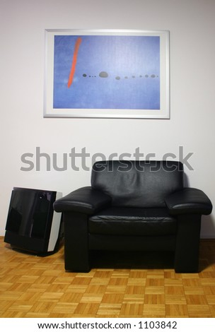 nice arm-chair in the living room with TV and picture