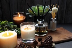 nice aromatic scented candle glass and reed diffusers  lighting on wooden holder on black wooden table with dried potpourri , herbs and spices pinecone in living room during Christmas new year party