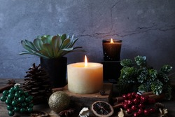 nice aromatic scented candle pillar lighting on the wooden holder on black wooden table with dried flowers , herbs and spices pinecone in the living room during Christmas new year party happy family