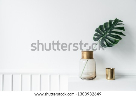 Nice artificial plant in glass vase with gold stainless trim edge and gold mirror vase setting on empty  fireplace in minimal modern style apartment / residential interior concept / copyspace