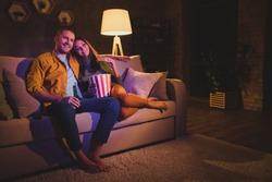 Nice attractive lovely cheerful cheery couple girl sitting on divan enjoying snack watching film spending day weekend holiday at night dark home house apartment indoors
