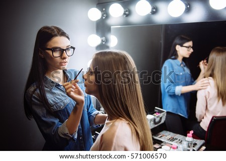 Nice attractive makeup artist using a cosmetic brush #571006570