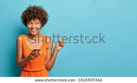 Nice attractive young Afro American woman uses cell phone and points on copy space shows direction dressed in stylish orange dress isolated over blue background. Ethnic lady with modern device