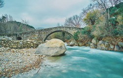Nice autumnal landscape of an old Roman bridge with a river with a lot of water flow. Jarandilla of La Vera. Spain