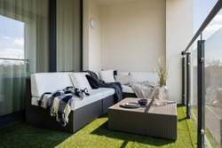 Nice balcony with rattan corner sofa and coffee table and synthetic grass on the floor