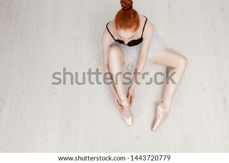 Nice ballerina sits on the white floor and dresses a beige pointe shoe in the studio. She wears a light dance wear and a peach tutu. Top view photo. Horizontal. Copy space