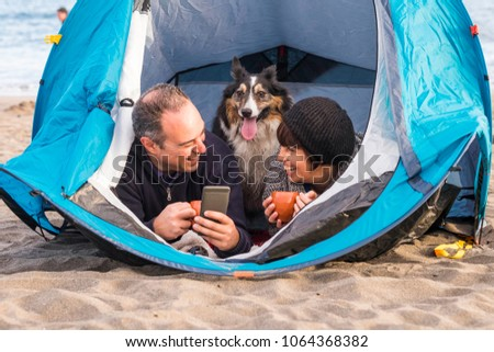 nice beautiful paople with cute puppy inside a tent using cellular phone to send message or take picture. beach camping freedom alternative vacation in tenerife with your best friends dog