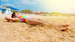 nice beuaitufl caucasian young girl lay down sleeping and relaxing on the sand at the beach. holiday for the child traveler laying down on the ground