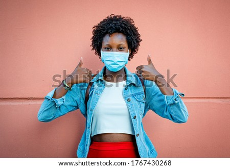 nice black girl, smiling with the eyes and wearing protective and medical mask, making the gesture of thumbs up, positive and optimism, over pastel coral pink background, vignetting effect Stockfoto ©